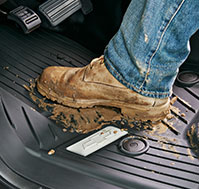 View of a man's muddy boots atop premium all-weather floor liners.