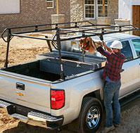 View of a construction worker attending to the utility rack on his Chevrolet pickup truck.