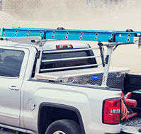 View of a ladder rack upfitted atop a GMC pickup truck.