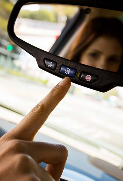 View of a woman pointing to the OnStar button on a GM Fleet vehicle's rear view mirror.