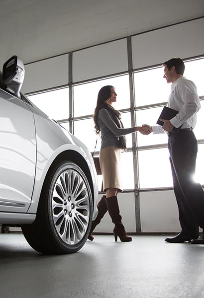 View of a woman shaking a GM Fleet dealer sales representative's hand.