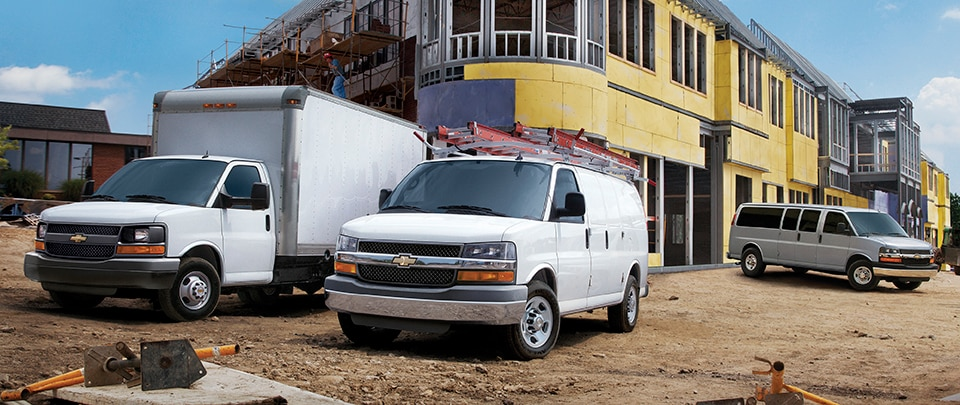 View of GM Fleet Chevrolet vans on a construction work site.